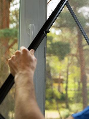 man replacing a dirty window screen